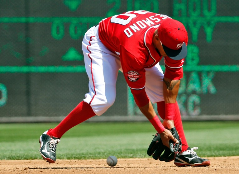 Washington Nationals shortstop Ian Desmond makes a fielding error on a ball hit by Philadelphia Phillies' Aaron Harang, who was safe at first after the play was reviewed, during the third inning of a baseball game at Nationals Park, Saturday, April 18, 2015, in Washington. (AP Photo/Alex Brandon)
